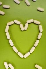 White pills on green background, heart shape