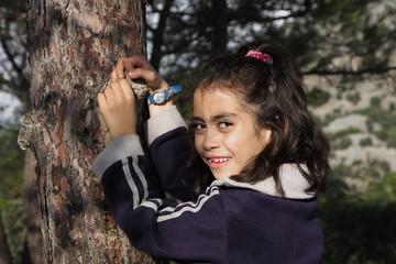 Mädchen lehnt am Baum