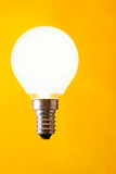 Shining light bulb close-up over yellow background poster