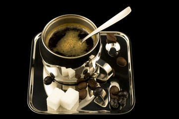 Metal coffee cup with spoon and sugar isolated on black