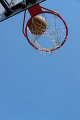 Basketball hitting the backboard net against clear blue sky
