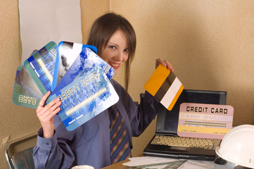 Young business woman holding online credit cards at office