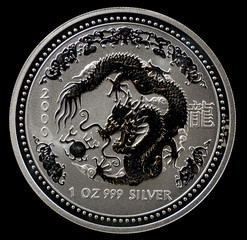 Australian silver coin with dragon, isolated on black background