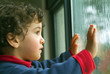 little boy watching the rain through the window