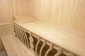 wooden bench of steam room in sauna with beautiful carving