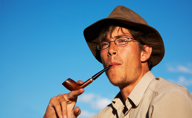 man in hat is smoking tobacco-pipe