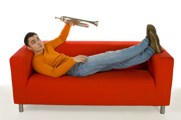 Thoughtful trumpeter lying on red couch and holding trumpet