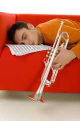 Sleeping trumpeter lying on red couch