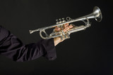 Somebody holding trumpet on dark background.