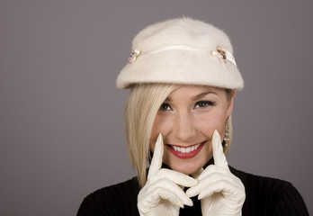 A blonde model with white fur hat and gloves smiling