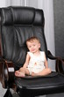 Very important small kid sits on real boss leather chair