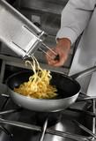 Chef preparing pasta on professional kitchen in restaurant poster
