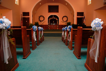 church aisle with blue ribbons