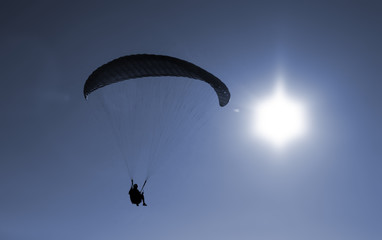 Paraglider flying agains the sun on sunset