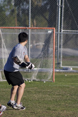 Asian lacrosse player takes a shot at an empty net