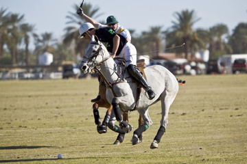 Two polo players nearly collide near ball