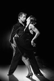 Fototapety Couple dancing hot latin dance on a street at night