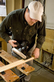 Man in workshop with skillsaw cutting a piece of wood poster