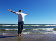 Man with  arms outstretched standing on the lakeshore
