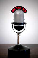 Retro microphone with an 'On the Air' illuminated sign on a desk