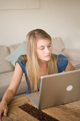 A blonde girl at home using a laptop computer