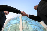 Two business men shaking hands in agreement poster