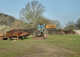 Old Tractor and rusty Trailer parked in a farmyard  poster