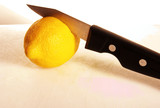 Knife cutting into a lemon.