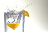 A lemon half splashing into a glass of water.