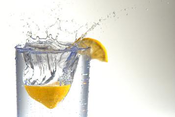 A lemon half splashing into a glass of water.