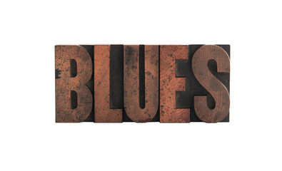 the word 'blues' in old, ink-stained wood letters