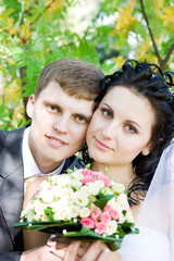 a portrait of the happy bride and groom with a flower bouquet