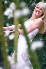 young blond bride behind flowers