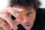 Man looking at drug capsule in this hand . poster
