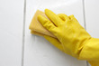 Hand in yellow glove with sponge, washing bathroom's wall