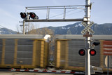 railroad crossing with a moving train in blur