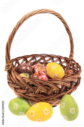 The wooden basket filled with Easter eggs - isolated on white