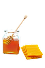 Drizzler inside of honey jar and honeycomb on white background.