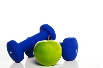 Two blue weights and a green apple
