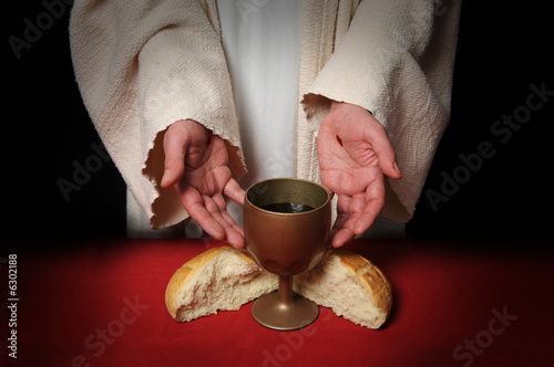 Leinwanddruck Bild The hands of Jesus offering the Communion wine and bread