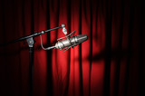 Vintage microphone with spotlight over a red curtain poster