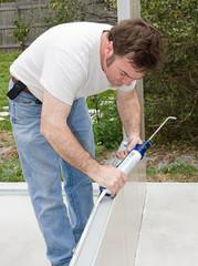 Handyman using a caulking gun to caulk a home