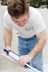 Handyman using a caulking gun to caulk a window.