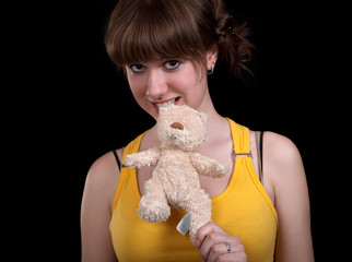Young girl with teddy-bear isolated at the black background