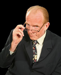 Middle aged businessman looks over the top of his glasses.