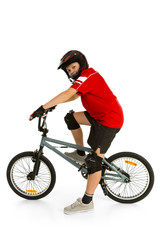 Happy boy in helmet on BMX and looking at camera
