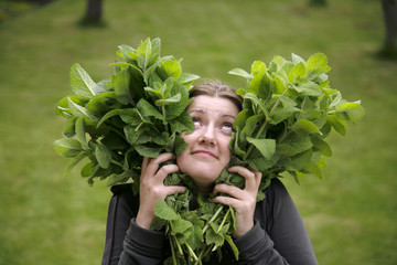 girl with heart shaped peppermint leaves in hands
