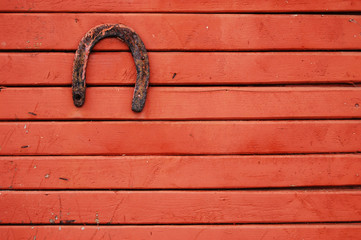 Old lucky horseshoe on red wooden wall