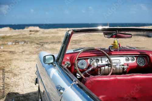 Papiers peints Caraibes cuban vintage car parked on the seacost in havana