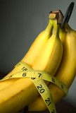 Measureing tape around some bananas.